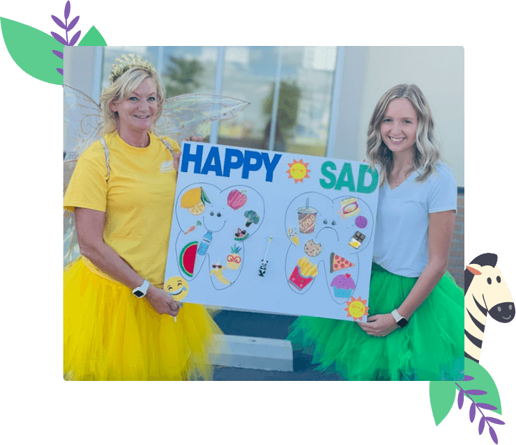 Two women holding up a sign with certain foods organized as happy or sad foods